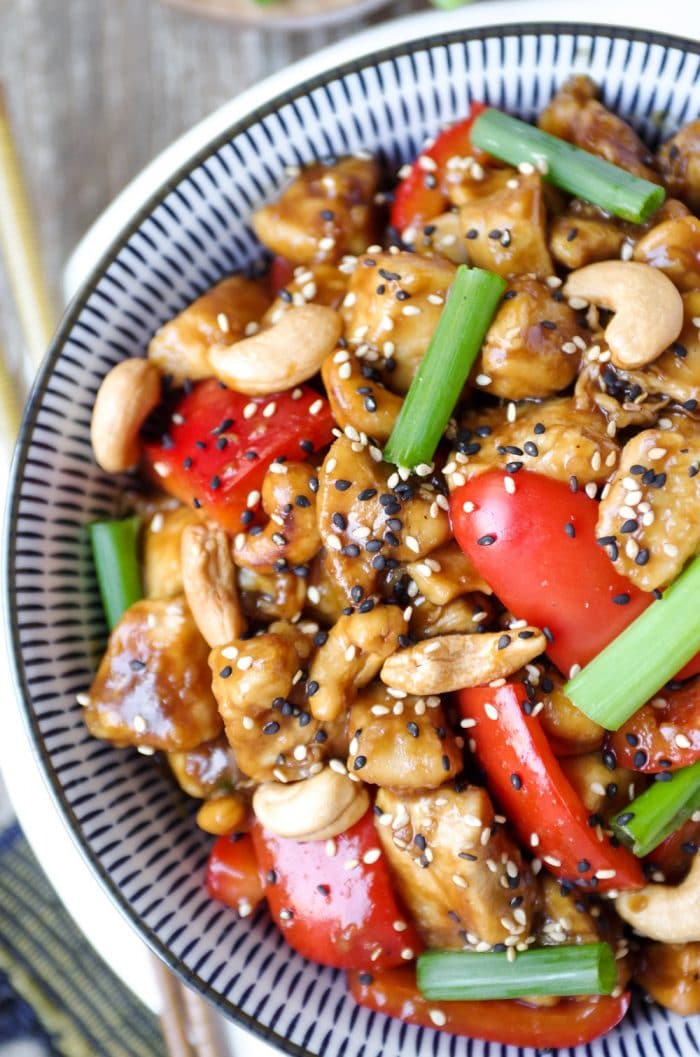 Close up image of cashew Chicken in a large blue and white serving bowl garnished with sesame seeds and green onions.