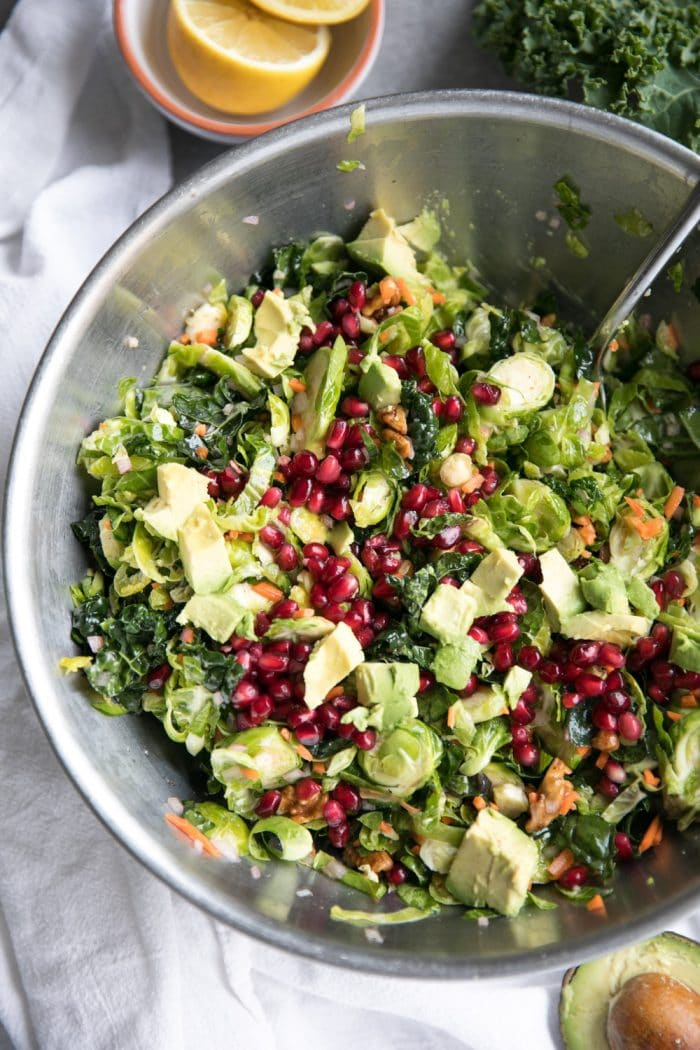 Large mixing bowl filled with kale, Brussels sprouts, pomegranate arils, avocado, and grated carrots mixed with lemon vinaigrette.