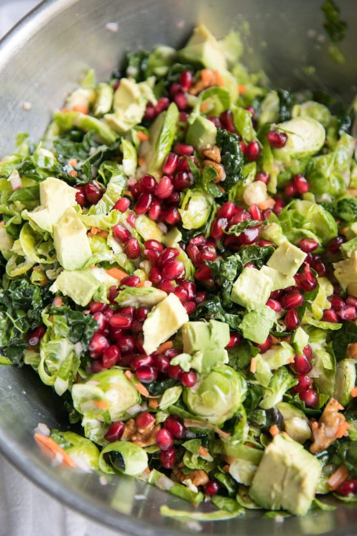 Close up of a large mixing bowl filled with shredded Brussels sprouts, kale, avocado, grated carrot, pomegranate arils, tossed in a light lemon vinaigrette.