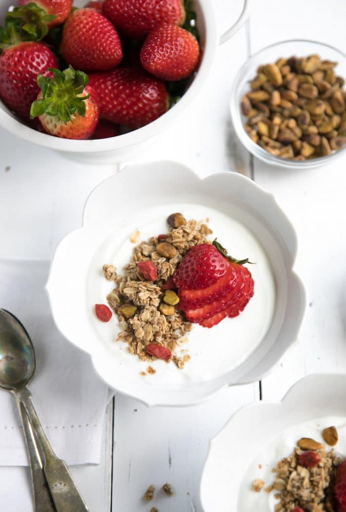 White bowl filled with plain greek yogurt and topped with homemade lightly sweetened granola.