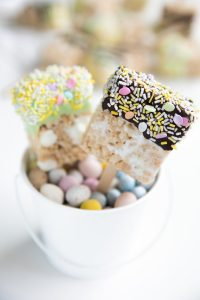 A close up of a chocolate-dipped rice Krispie treat squares
