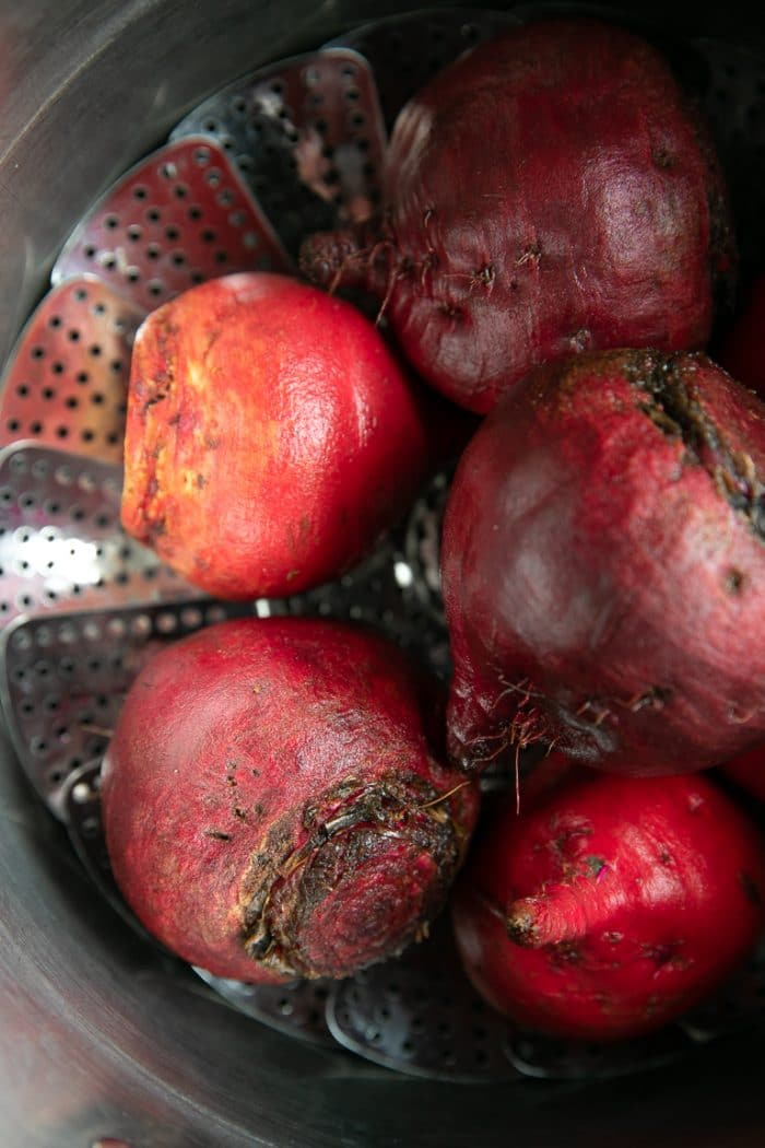 Raw beets in a large pot with a steaming basket.