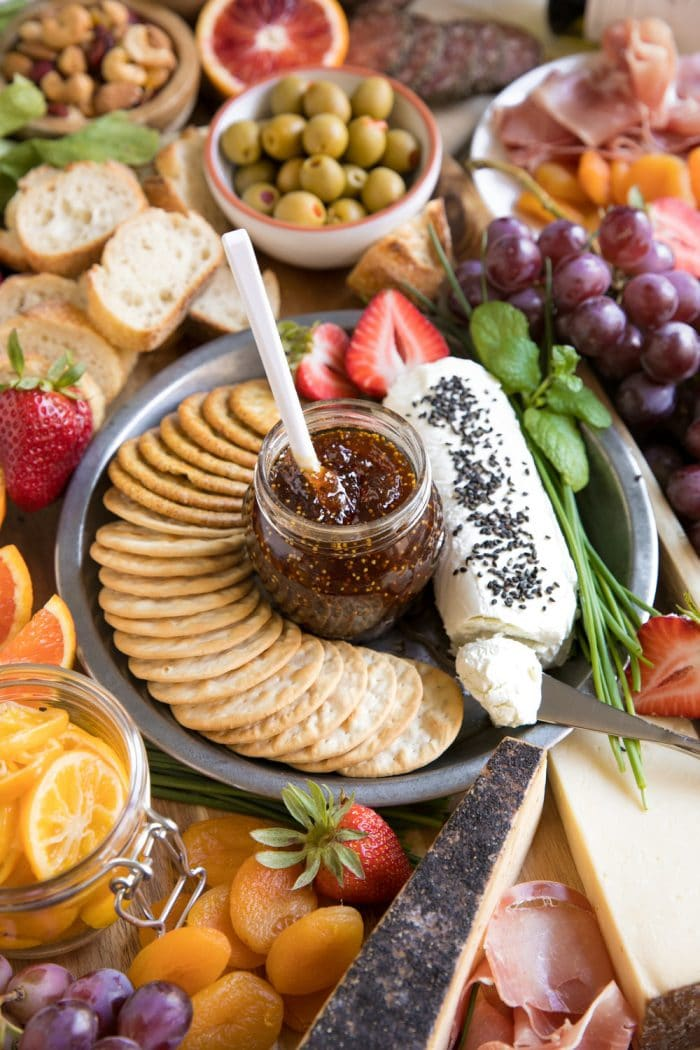 Colorful Spring Cheese Board with large assortment of meats cheese fruits and nuts with wine featuring fig jam in middle