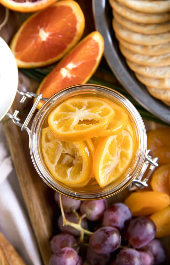 oranges in jar among grapes and crackers