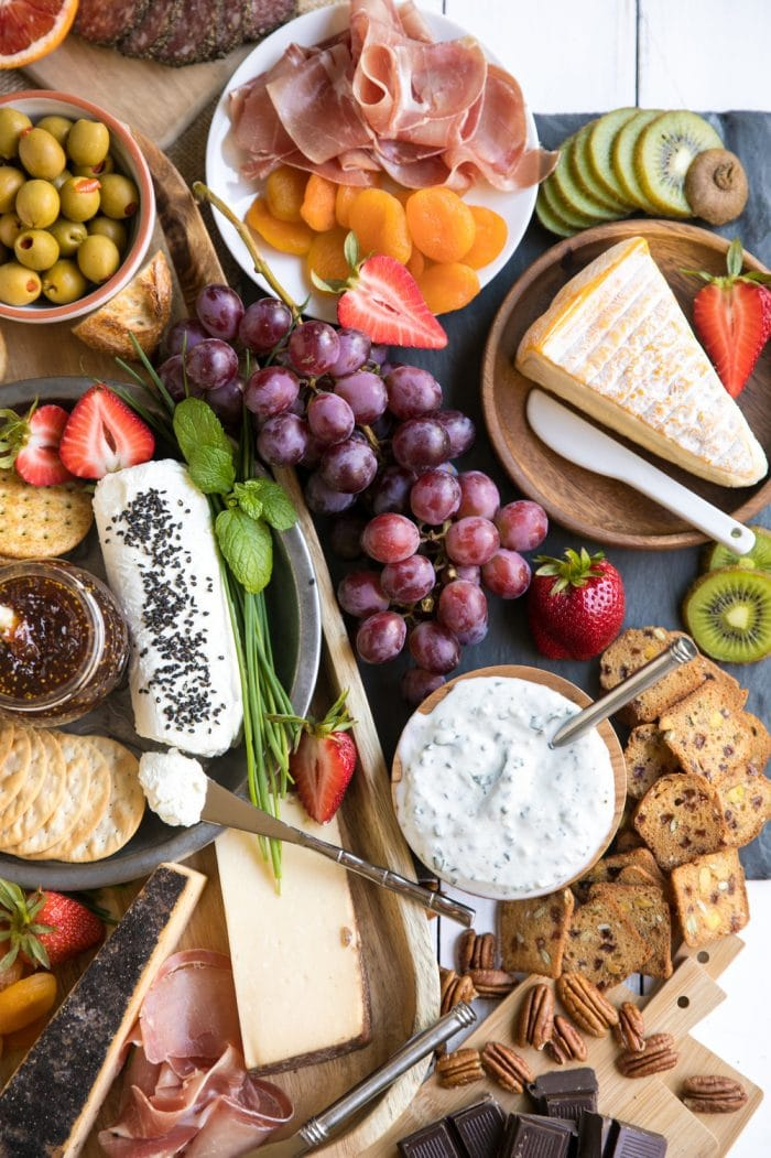 Colorful Spring Cheese Board with large assortment of meats cheese fruits and nuts with wine