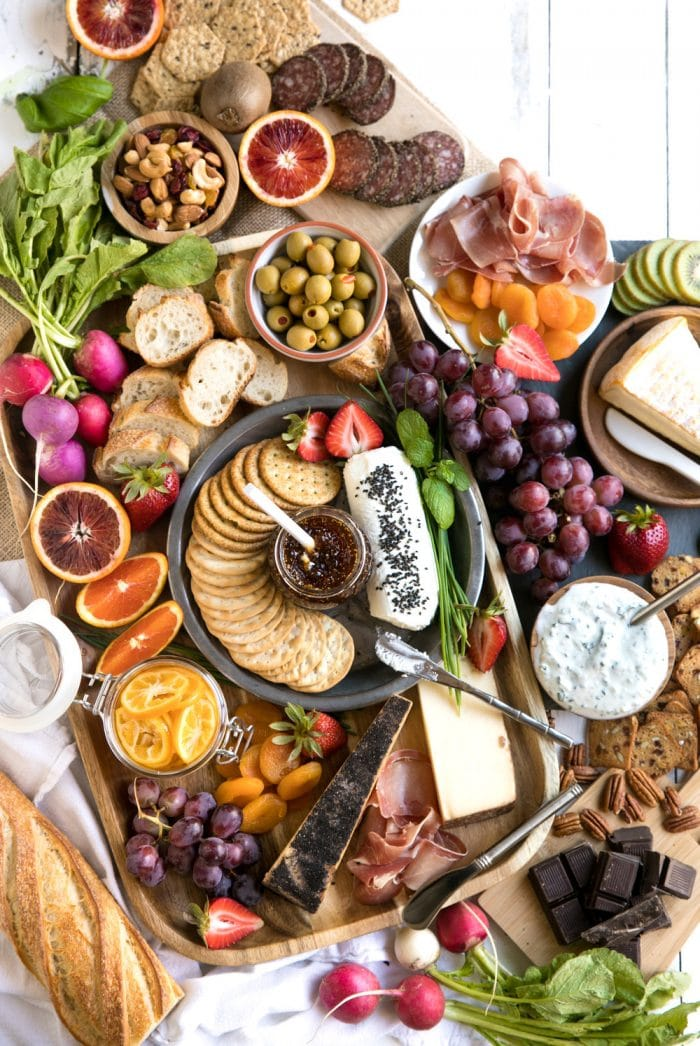 close up of Colorful Spring Cheese Board with large assortment of meats cheese fruits and nuts with wine