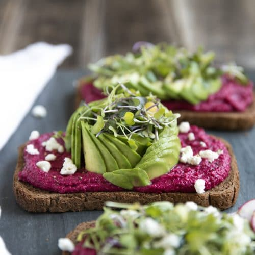 A close up of an avocado toast with beet hummus sitting on top of a table