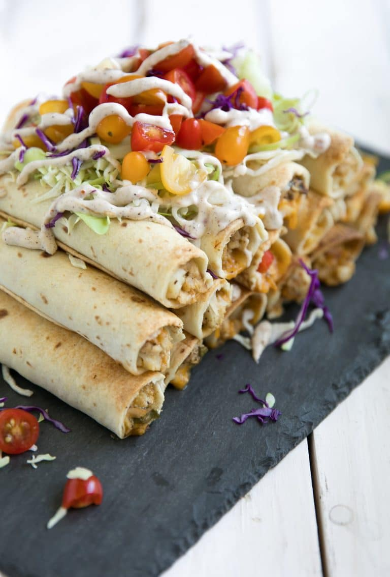 pile of Jerk Chicken and Cauliflower Taquitos covered in vegetables and sauce