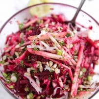 Glass bowl filled with raw beets, shredded kohlrabi, apples, green onion, feta, and sunflower seeds all mixed together.