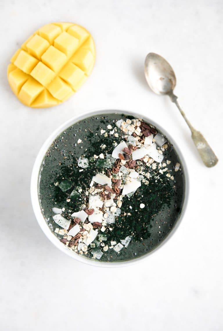 Almond Butter and Spirulina Smoothie Bowl with sliced mango and spoon