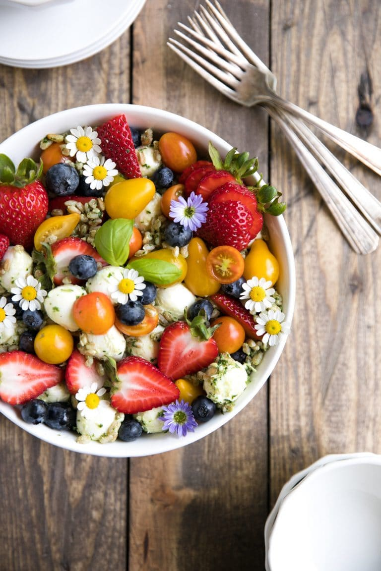 A bowl of fruit on a plate, with Farro and Salad