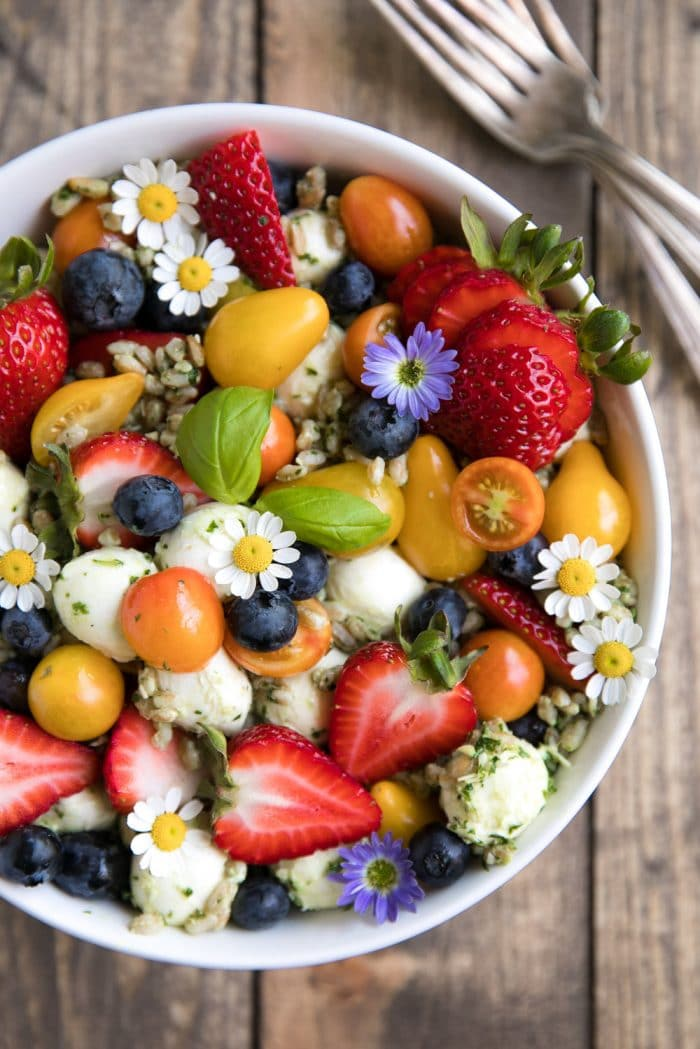 Overhead image of a large white bowl filled with farro tossed in homemade pesto and served mixed with fresh strawberries, blueberries, mozzarella cheese, and tomatoes.