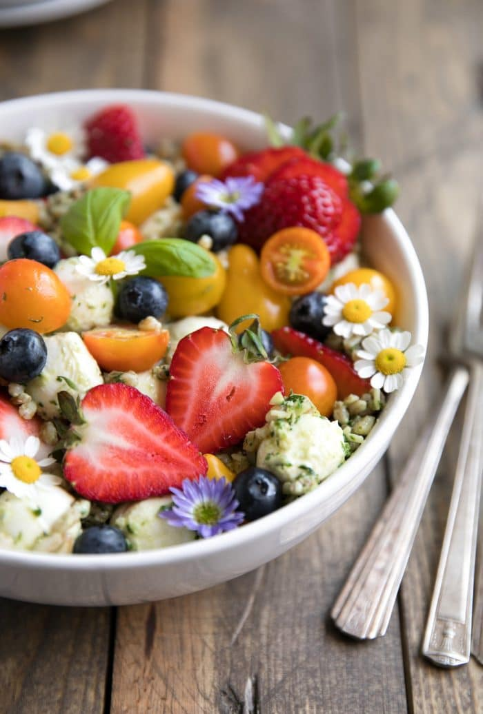 Large white bowl filled with farro tossed in homemade pesto and served mixed with fresh strawberries, blueberries, mozzarella cheese, and tomatoes.