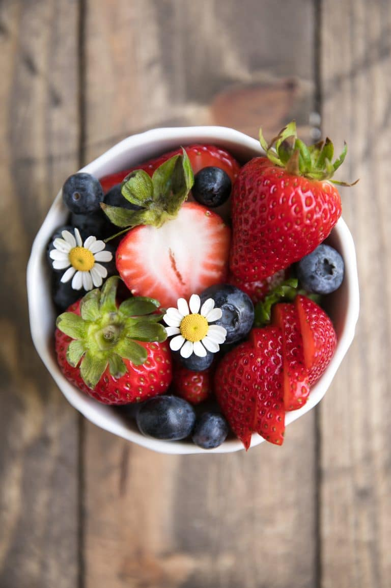 close up of flowers in fruit dish of strawberries and blueberries