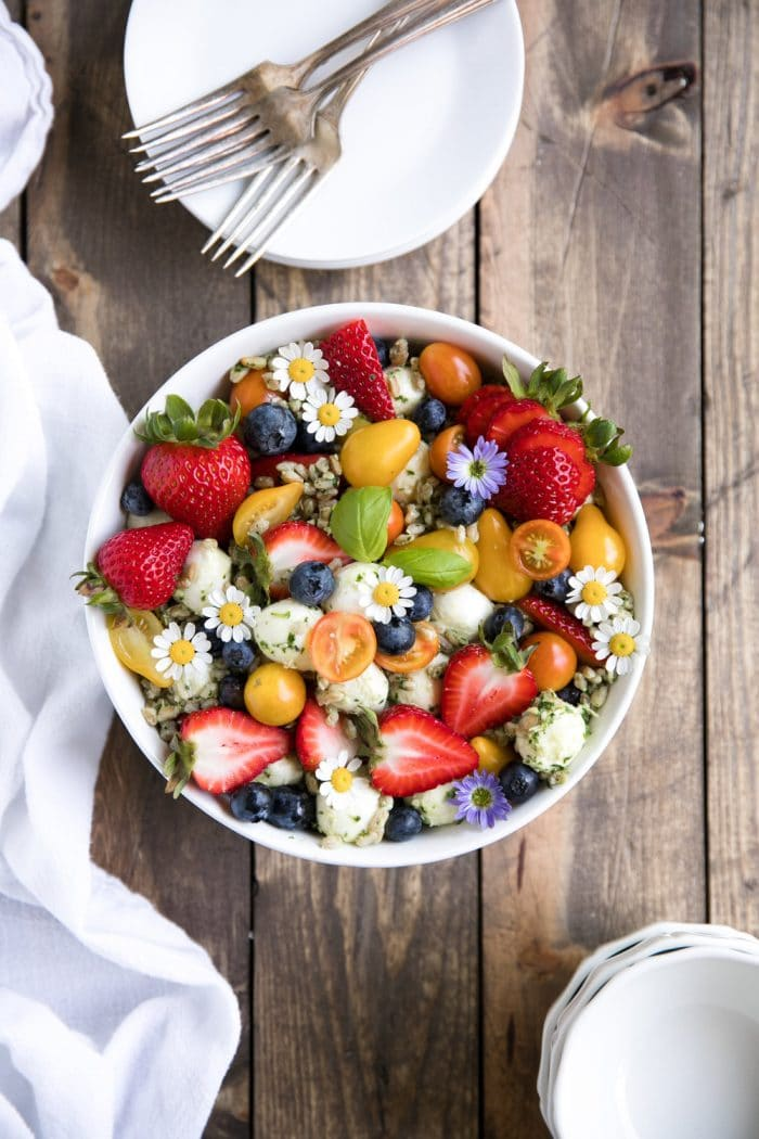 Caprese farro salad with fresh berries, tomatoes, mozzarella cheese, and basil pesto in a large serving bowl.