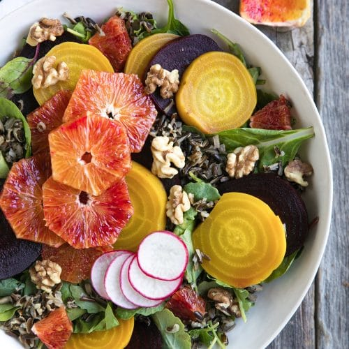 Large white serving platter topped with fresh leafy greens, sliced golden and red beets, bloof oranges, cooked wild rice, walnuts, and sliced radish.
