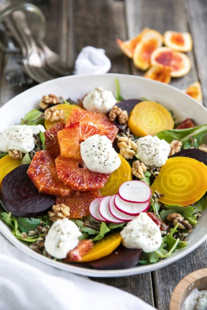 Large white serving platter topped with fresh leafy greens, sliced golden and red beets, bloof oranges, cooked wild rice, walnuts, and whipped lemon ricotta.