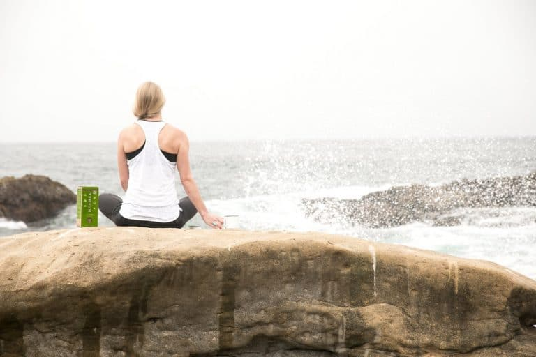 jessica sitting on rock with waves crashing in front holding cup next to bota box