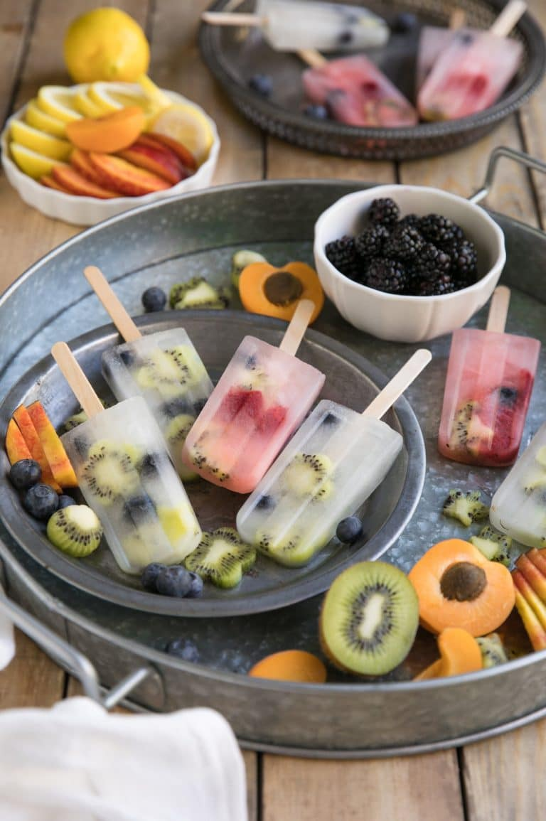 6 translucent Lemonade and Fruit Popsicles with whole fruit visible on inside