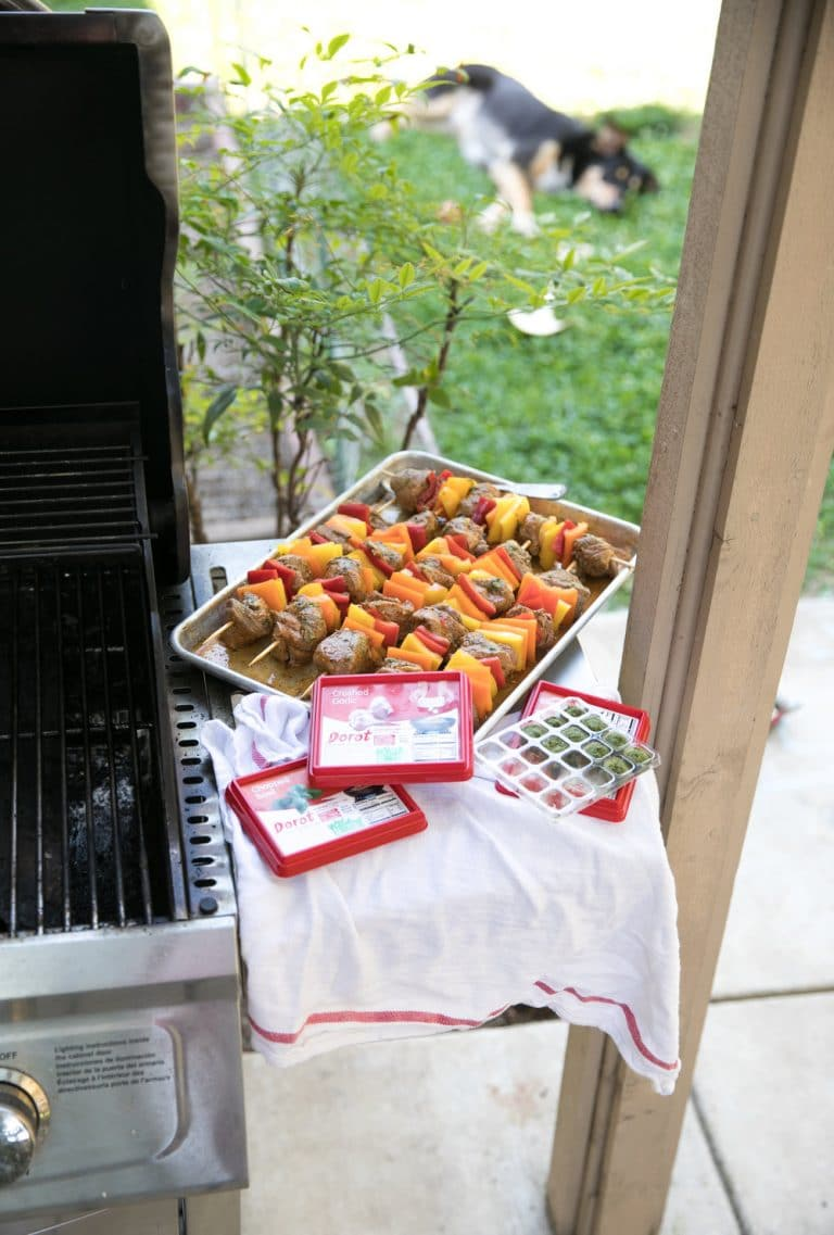 lamb kebabs next to grill outside