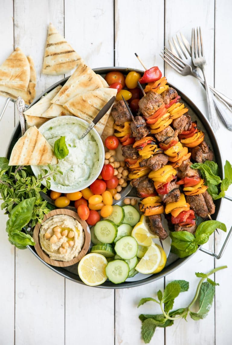 A bunch of food on a plate, with Cheese and Kebab