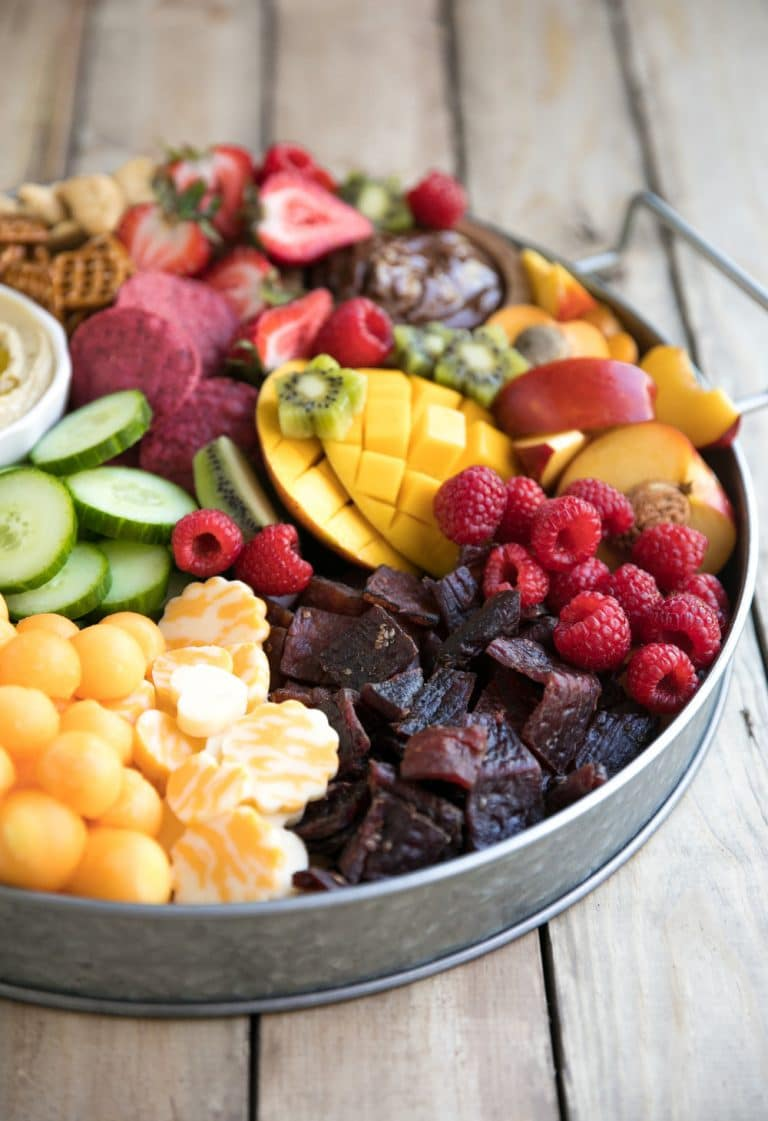 Bright, colorful, and jam-packed with delicious snacks both kids and adults will love, this super easy Kid-Friendly Charcuterie Board will be the highlight of any party! Filled with fresh fruit, cheese, meat snacks, nutella, hummus, and fresh chopped veggies.