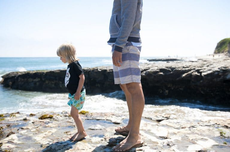 father and son standing near ocean