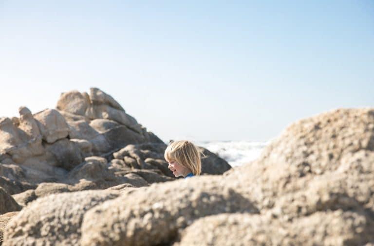 boy playing in coastal rocks