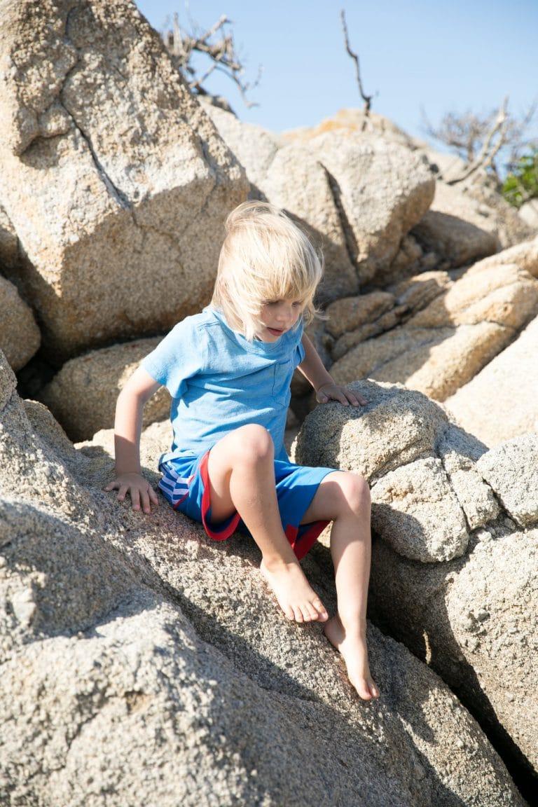 young boy climbing down rocks