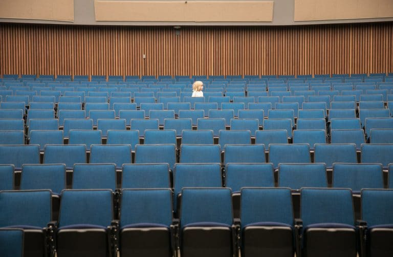 boy walking in row of empty lecture hall seats