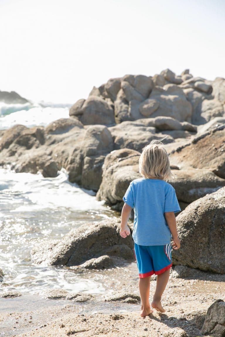 boy playing on rocky beach