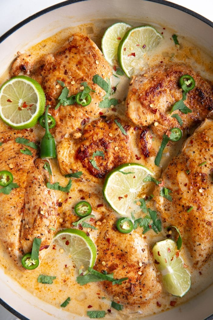 Large white enameled skillet filled with thinly sliced chicken breasts simmering in a homemade sauce made with coconut milk, chicken broth, and lime juice, and garnished with lime slices and fresh cilantro.