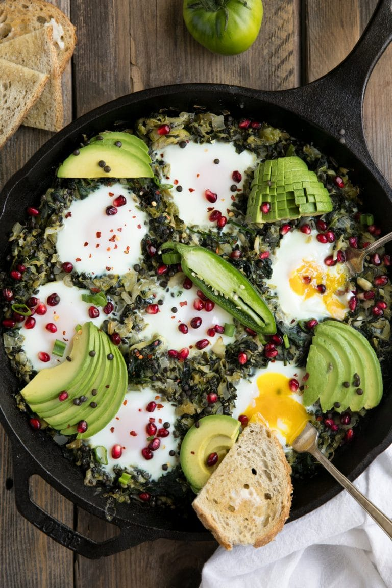 Green Shakshuka in cast iron pan with buttered bread