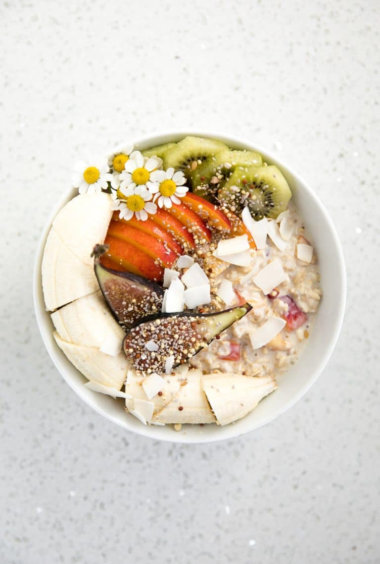 overhead photo of bowl of Peach Overnight Oats with flowers