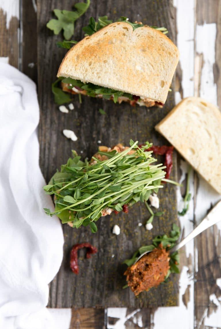 Sun-Dried Tomato Pesto Chicken Salad Sandwich cut in half with greens and pesto sauce
