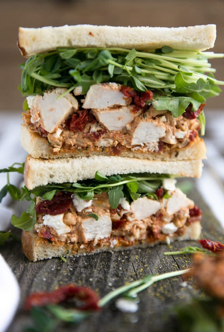 two halves of Sun-Dried Tomato Pesto Chicken Salad Sandwich stacked on eachother