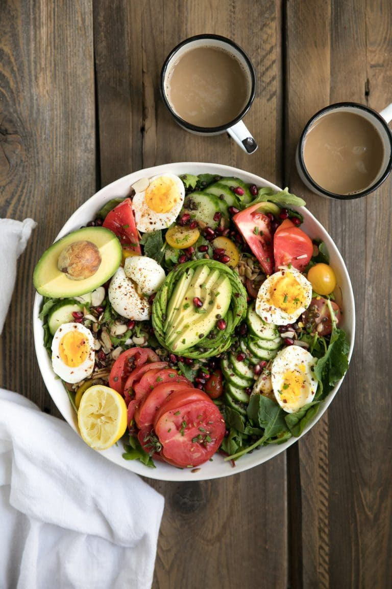 overhead image of Rocket and Beluga Lentil Breakfast Salad in bowl with two mugs of coffee