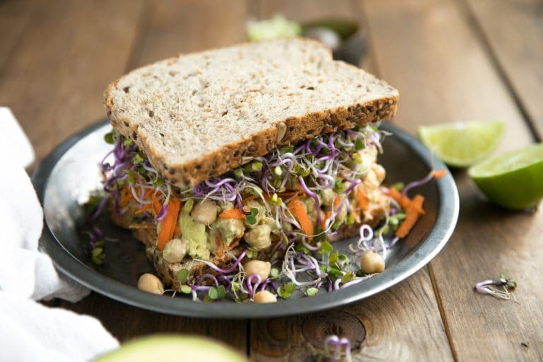 Smashed Avocado and Chickpea Sandwich with chickpeas falling out