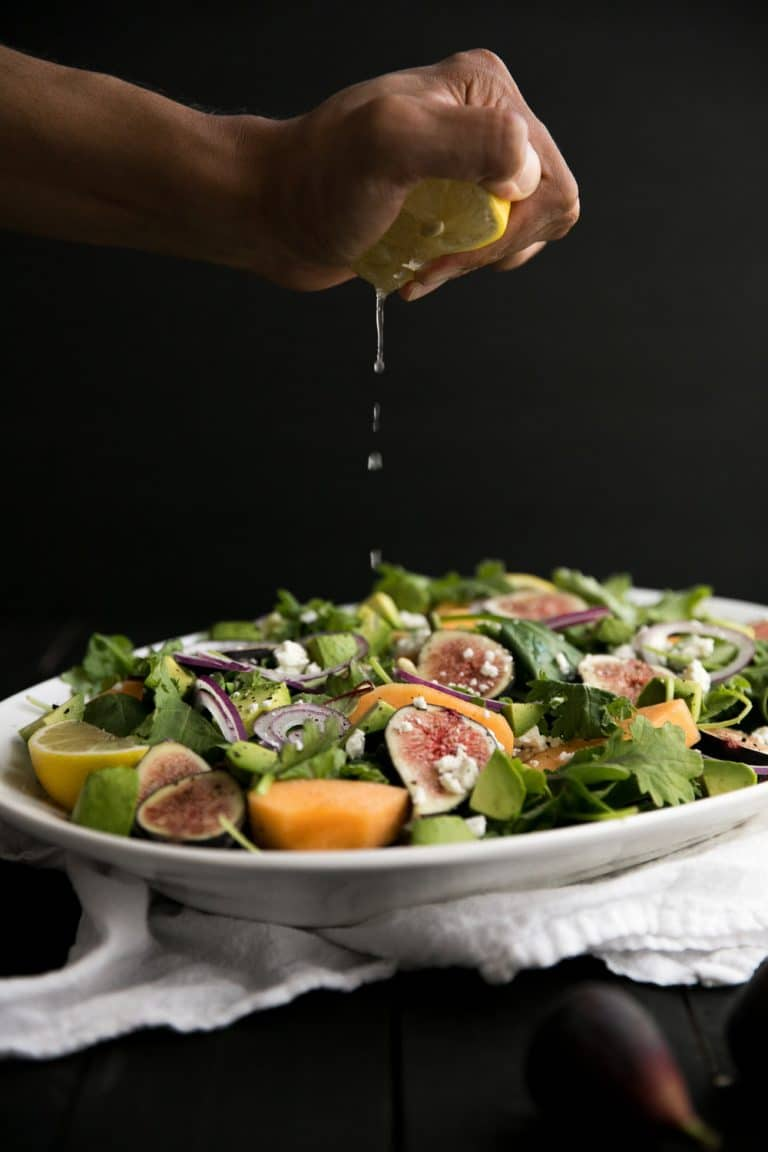 hand squeezing lemon onto Fig and Melon Salad