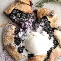 Homemade rustic galette made with blackberries and blueberries and topped with a big scoop of vanilla ice cream.