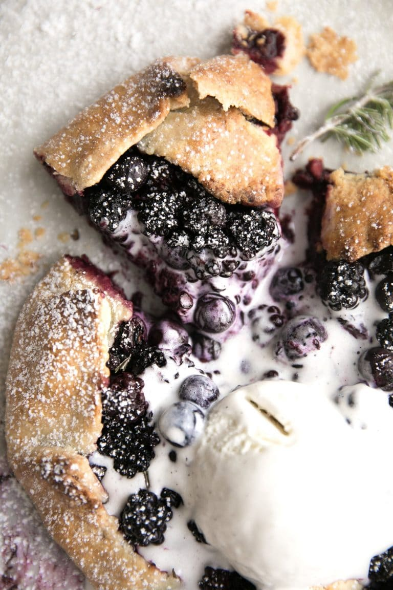 Rustic Blackberry and blueberry Galette. Fresh juicy blackberries and blueberries and hints of fresh rosemary all baked inside a homemade flakey, buttery crust.