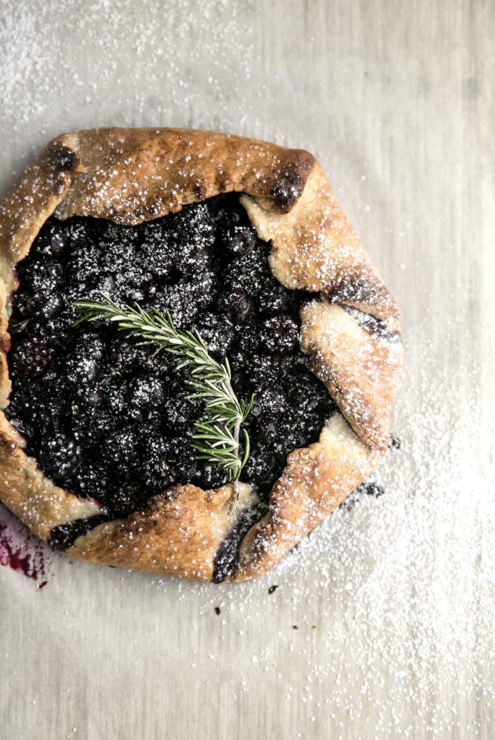 Overhead image of homemade butter blueberry galette dusted with powdered sugar.