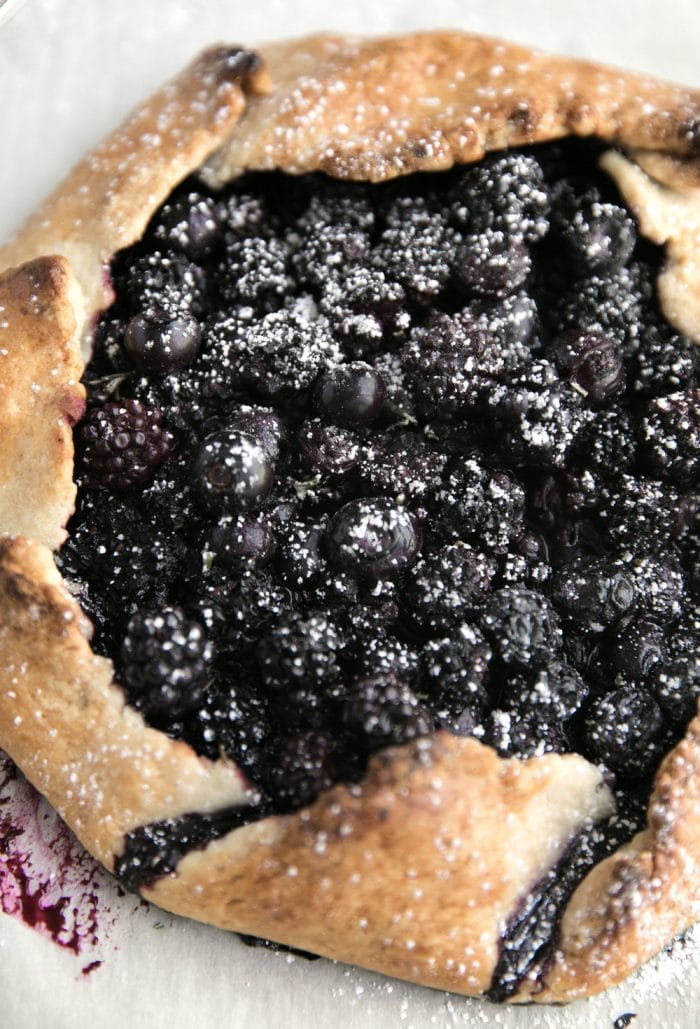 Closeup image of a galette made with blackberries and blueberries and dusted with powdered sugar.