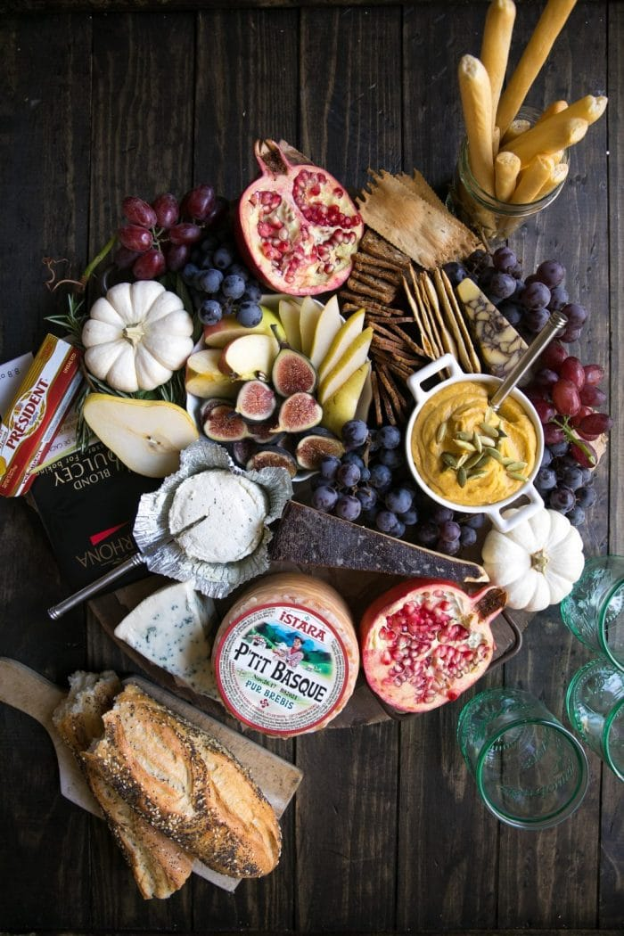 Cheese board filled with fresh fruits like figs, pears, grames, and pomegranates, soft and hard cheeses, dips and crackers.