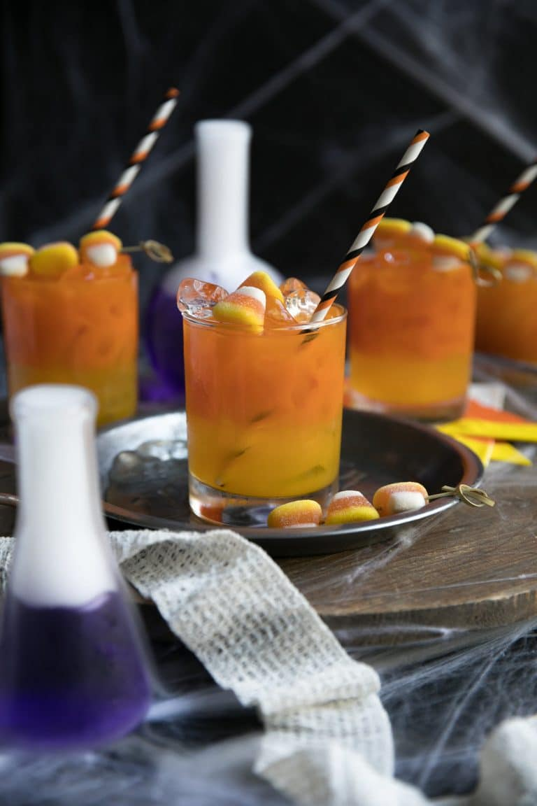spooky photo of Candy Corn Inspired Carrot and Orange Juice Gin Cocktail with dry ice in purple beakers