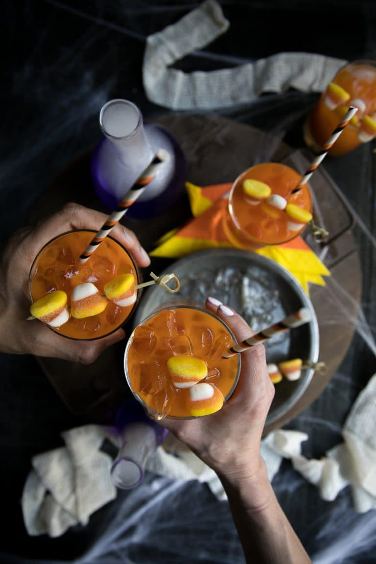two hands cheering cocktail glasses