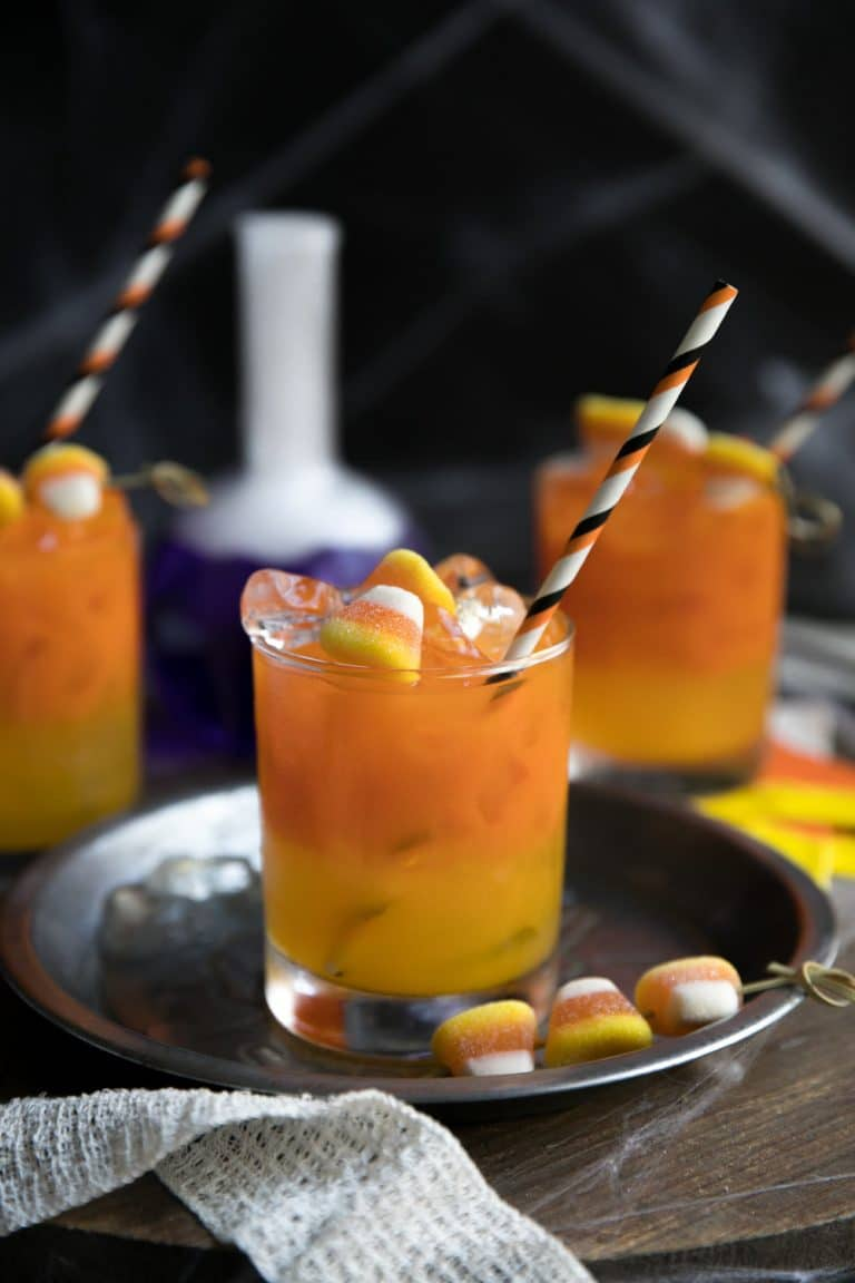 three glasses of Candy Corn Inspired Carrot and Orange Juice Gin Cocktail with purple beaker emitting fog in the background