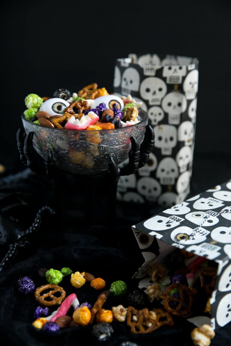 bowl of Halloween Monster Mash Party Mix with two bags on side