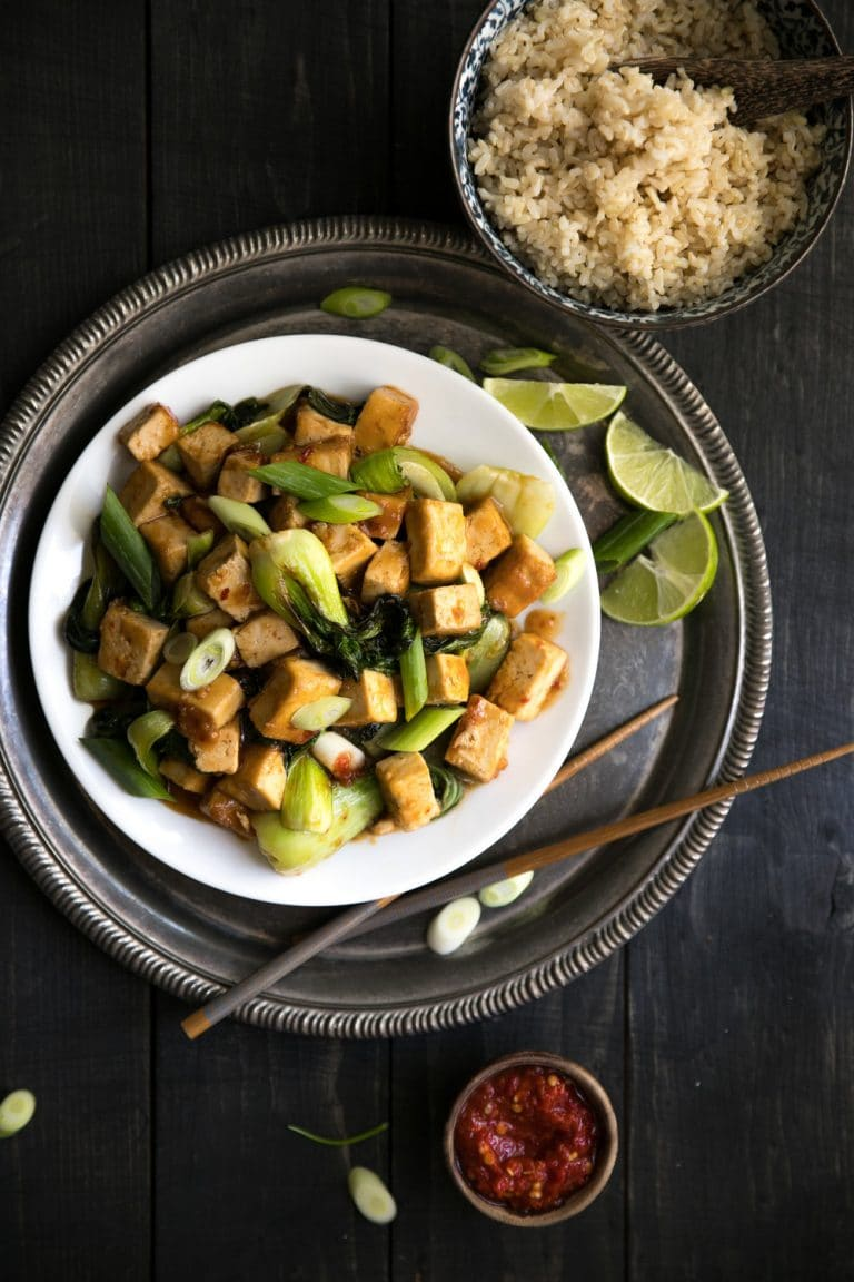 Spicy Stir Fried Tofu with Bok Choy plated with a bowl of rice on the side with a small dish of chili paste