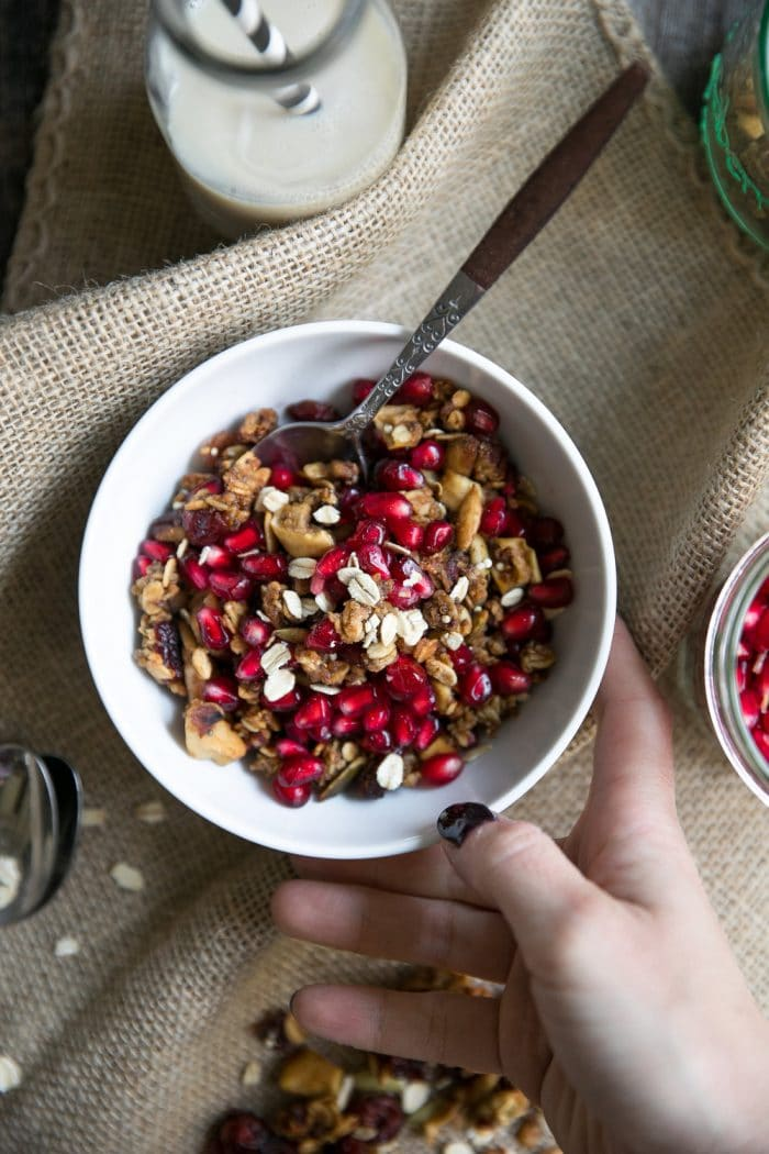 Image of a hand holding a white bowl filled with granola that's been toasted with autumn spices, and pomegranate arils.